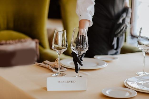 白いお皿、グラス、レストランで受け取ったネームプレート付きのランチテーブルクロス。焦点は眼鏡にあります