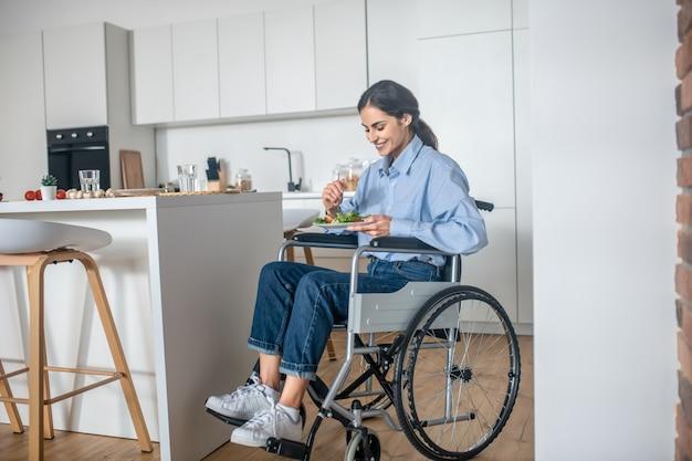 점심 시간. 집에서 점심을 먹고 있는 긍정적인 장애인 젊은 여성