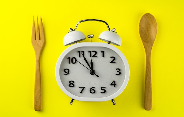 Lunch time with alarm clock on yellow background.