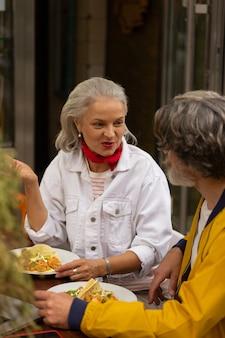 점심 같이 먹자. 행복한 여자는 거리 카페에서 남편과 함께 이야기하고 식사를 합니다.