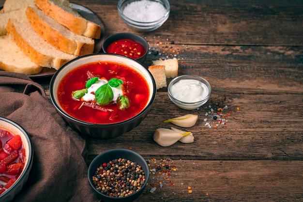 자연 나무 배경에 사 우 어 크림과 마늘 보르시와 함께 점심 식사. 전통적인 조리법의 개념.