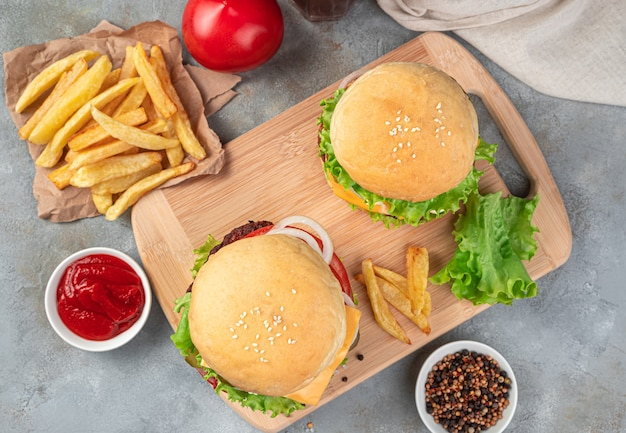 ハンバーガーと一緒にランチ。灰色の背景に2つの大きなハンバーガー、フライドポテトとグレービー。上面図。