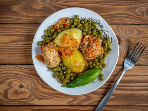Lunch with chicken meatballs with rice and vegetables and canned green peas table fork top view