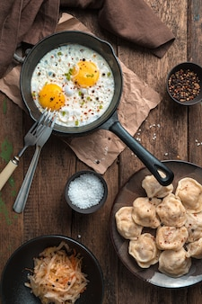 Обед с яичницей и клецками на деревянном фоне. вид сверху, вертикальная ориентация. концепция приготовления пищи.