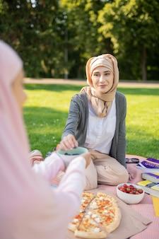 친구와 점심. 친구와 함께 맛있는 점심을 먹고 hijab를 입고 아름다운 이슬람 여자