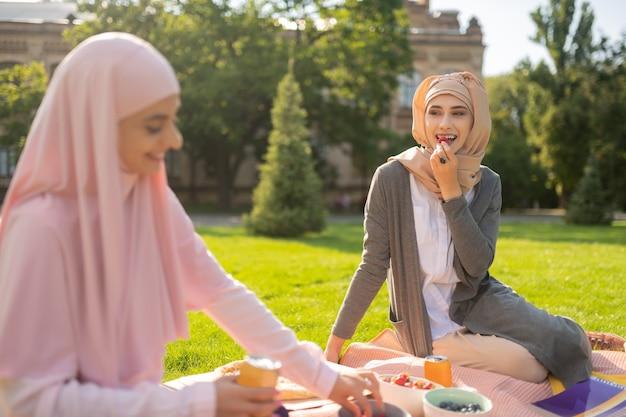 친구와 점심. 친구와 점심을 먹으면서 딸기를 먹는 히잡을 입고 이슬람 여성