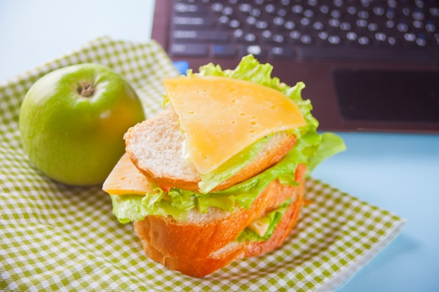 Lunch with sandwich and green apple and laptop on the table.