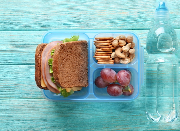 Lunchbox and bottle of water on wooden background
