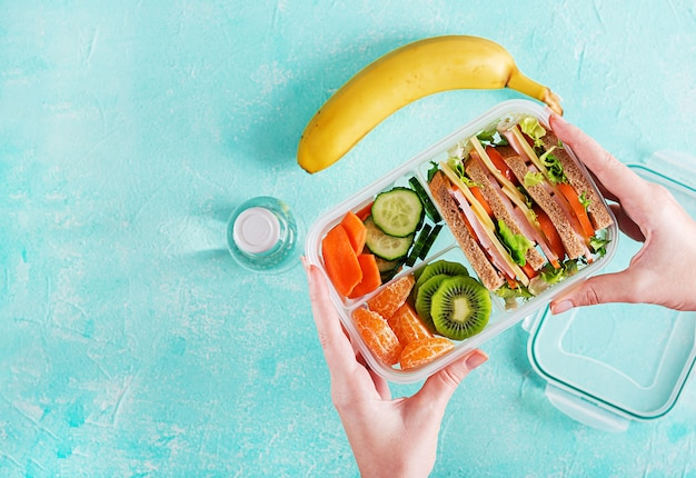 Lunchbox in hands. school lunch box with sandwich, vegetables, water, and fruits on table. healthy eating habits concept. flat lay. top view