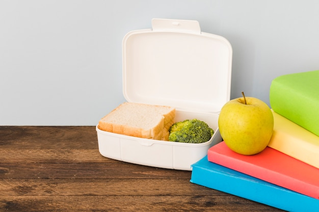 Lunchbox near apple and colorful books