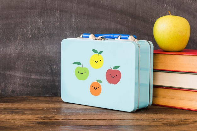 Lunchbox near stack of books and apple
