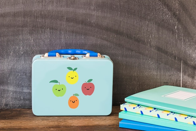 Lunchbox near stack of notebooks