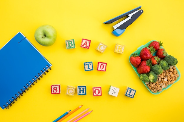 Lunchbox and stationery with writing on table