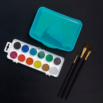 Lunchbox, watercolors and brushes on blackboard