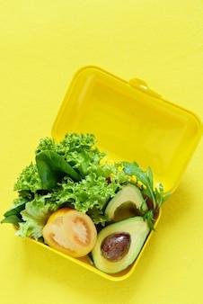 黄色の壁にレタス、トマト、アバカドのスナックが入ったお弁当。健康的な食事のコンセプトです。ビーガンに行きますプラスチックの箱でおいしいベジタリアン料理。