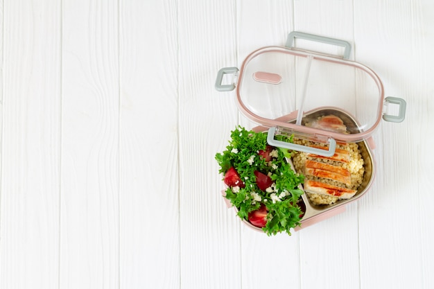 Lunchbox with balanced food on wooden table top view with space for text