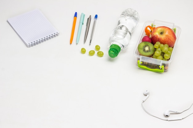 Lunchbox with fruits on table. notepad pens, headphones and bottle of water on white