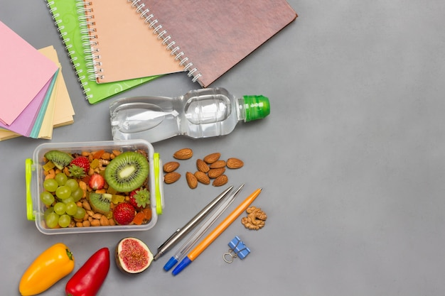 Lunchbox with nuts and fruits and pens and notebooks, flat lay