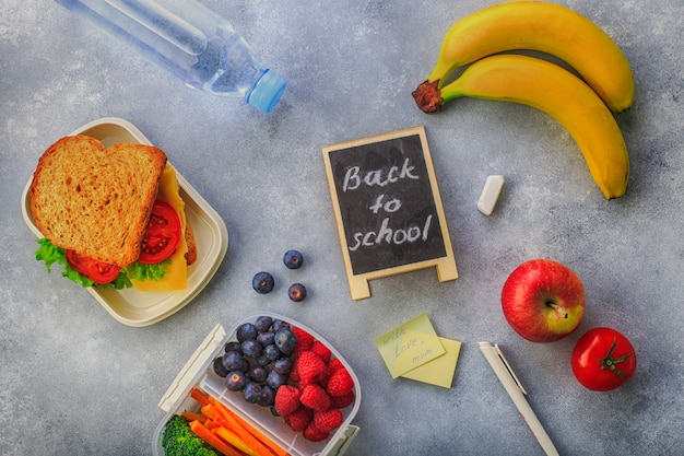 Lunchbox with sandwich berries carrots broccoli bottle of water banana on grey top view