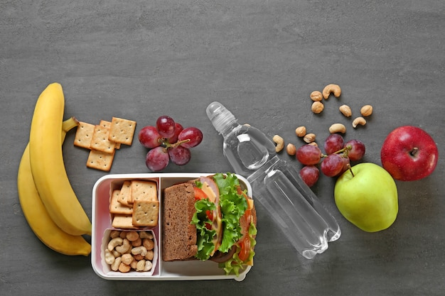 Lunchbox with sandwich and different products on dark background