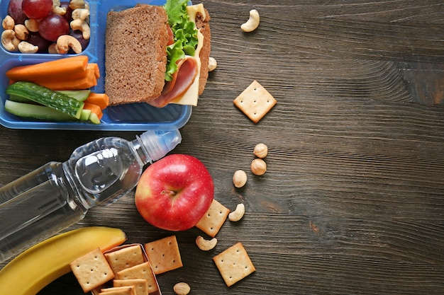 Lunchbox with sandwich and different products on wooden background