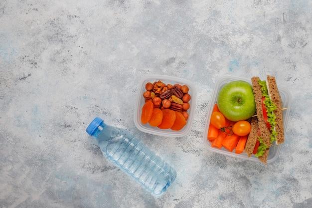 Коробка для завтрака с сандвичем, овощами, плодоовощ на белизне.