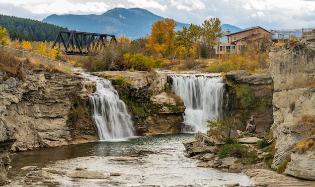 Водопад лундбрек, водопад реки кроуснест в осенний сезон листвы. железный мост для железнодорожных путей на заднем плане. альберта, канада.