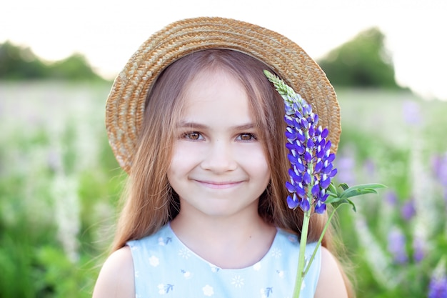 Красивая маленькая девочка в платье держа люпин на заходе солнца на поле. понятие природы и романтики. счастливое детство ребенок держит цветы возле его лица. летний закат. lupinus polyphyllus.