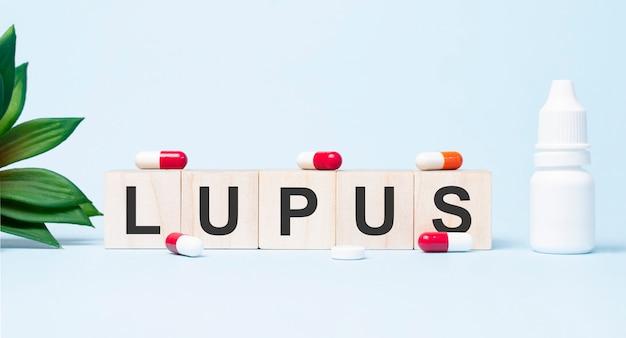 빌딩 블록으로 만든 lupus 단어. 검정색 글꼴로 쓰여진 단어가있는 나무 큐브 행은 흰색 배경에 있습니다.