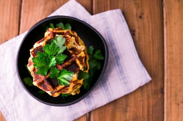Пышные бельгийские вафли с овощами и зеленью на деревянном столе. концепция здорового питания и вегетарианства. темное фото в деревенском стиле. свободное место для текста.