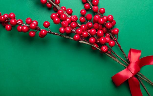 緑の背景の上にお祝いのリボンでクリスマスの装飾として赤い果実やガマズミ属の木と緑豊かな枝。