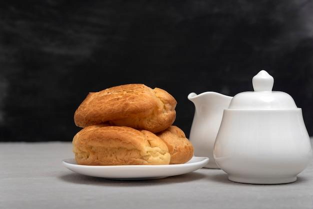 Пышные домашние эклеры и чайная посуда. французская выпечка.