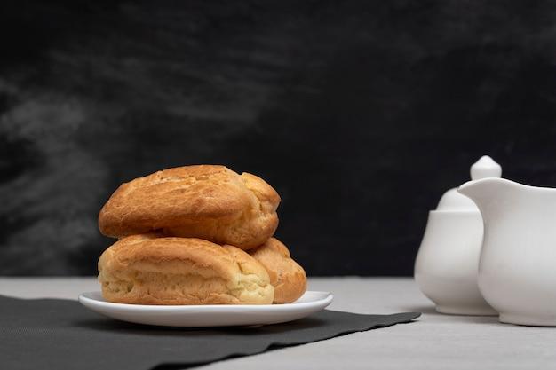 Пышные домашние эклеры и посуда для чая Premium Фотографии