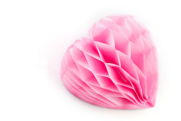 A lush pink paper heart on a white surface,