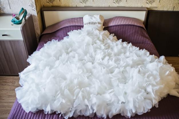 Пышное свадебное платье лежит на кровати