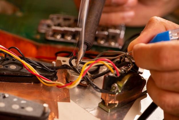 그의 작업실에서 기타 와이어를 납땜하는 Luthier 프리미엄 사진