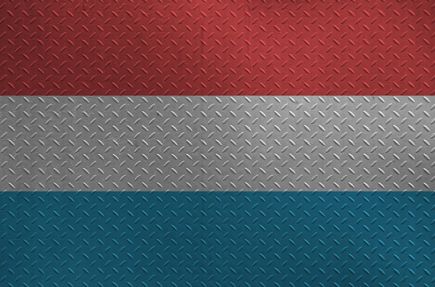 Luxembourg flag depicted in paint colors on old brushed metal plate or wall closeup. textured banner on rough background