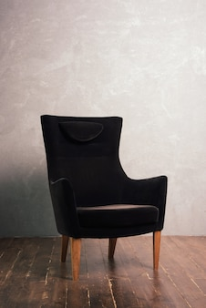 Luxurious black velor armchair stands near the textural wall on a dark wooden floor