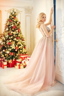Luxurious blonde in an evening dress near a christmas tree