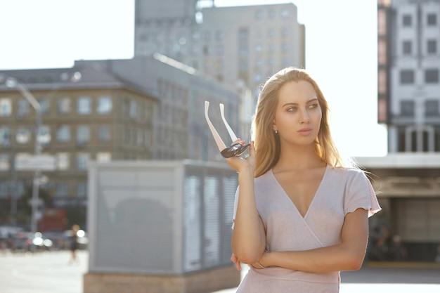 긴 머리를 가진 고급스러운 금발 모델은 선글라스를 들고 카메라를 바라보고 있습니다. 텍스트를 위한 공간