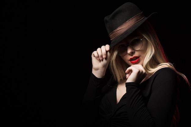 黒のブラウス、帽子、眼鏡を身に着けて、影でポーズをとる豪華なブロンドの女性