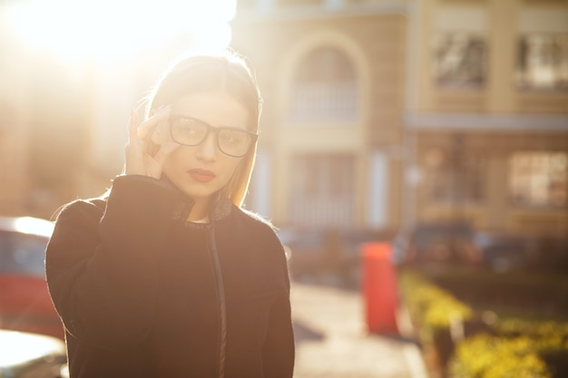 Luxurious blonde woman wears glasses and walking down sunny street. space for text