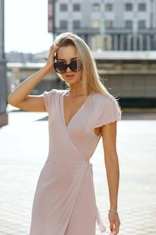 해질녘 거리를 걷고 있는 핑크색 드레스를 입고 긴 머리를 가진 고급스러운 금발 여성