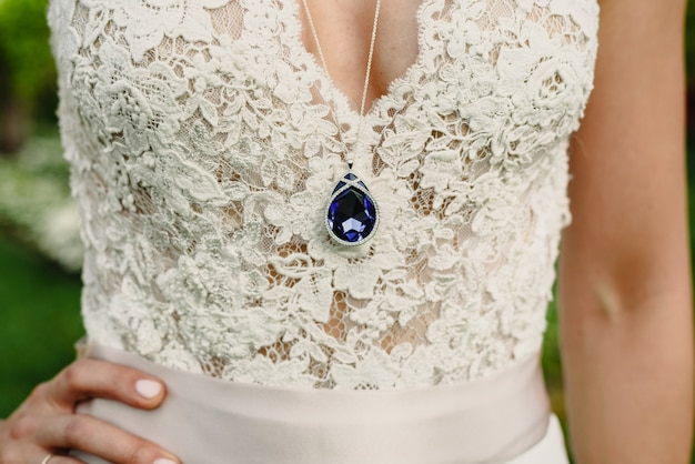 Luxurious blue sapphire jewel dangling from the chest of a bride and her dress.