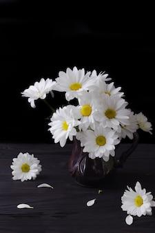 暗い背景の花瓶に大きな白いlevcantemellaデイジーの豪華な花束。
