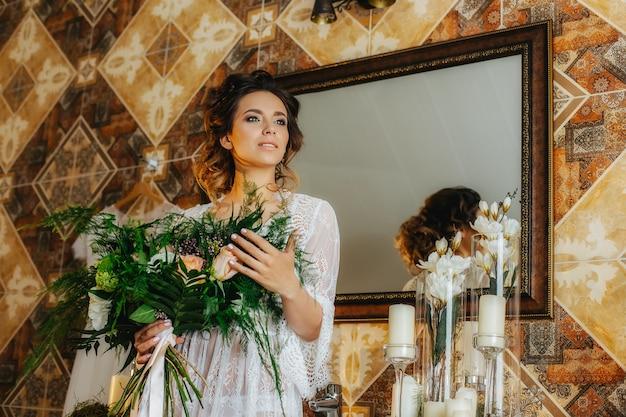 꽃과 녹지의 꽃다발과 함께 아름다운 레이스 가운에 고급스러운 신부
