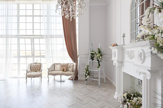 아름답고 세련된 가구가 있는 고급스럽고 밝고 넓은 객실, 왕실 스타일의 거대한 천장부터 바닥까지 내려오는 대형 창문은 녹색 식물, 치장 벽토와 벽난로가 있는 흰색 벽으로 장식되어 있습니다.