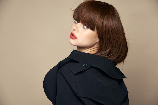 豪華なブルネットの黒いコートの魅力的な外観笑顔の屋内正面図