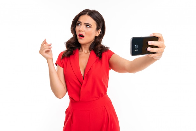 Luxurious brunette girl in a red dress makes selfie using the phone on white
