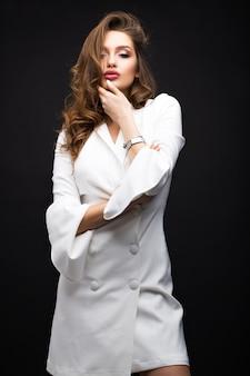 黒い背景に白いドレスの豪華なブルネット